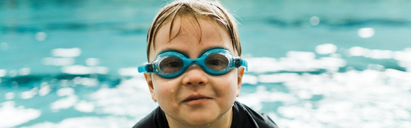 kid with goggles in pool